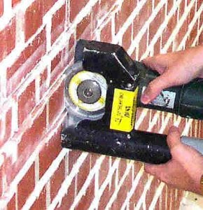 """Cutting vertical brick mortar joints. Notice the dust being """"directed"""" into the vacuum barrel."""